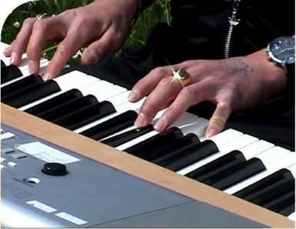 hands with tatoo playing piano